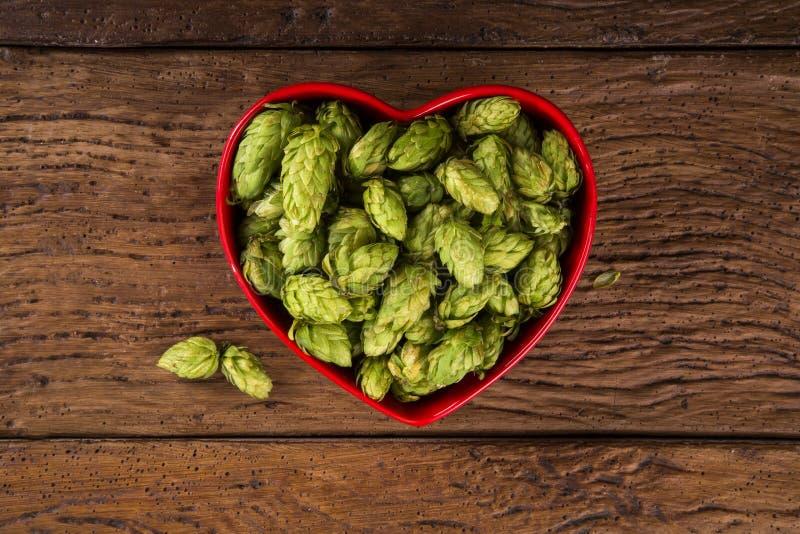 La cerveza que elabora los conos de salto de los ingredientes en corazón rojo rueda en fondo de madera Concepto de la cervecería  foto de archivo libre de regalías