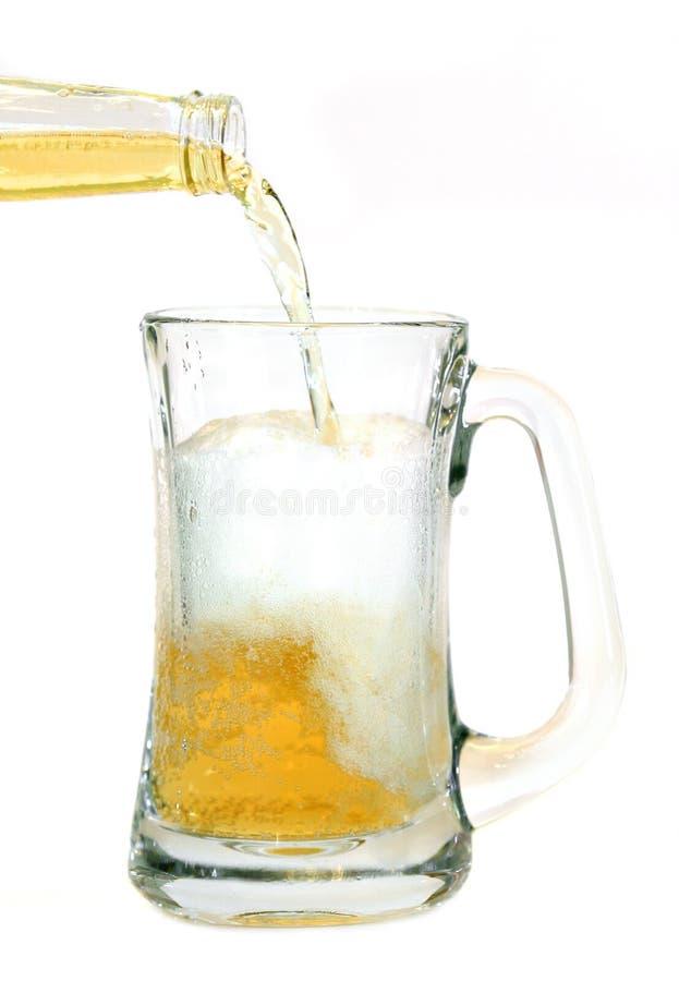 La cerveza vertió en la taza de cristal fotos de archivo