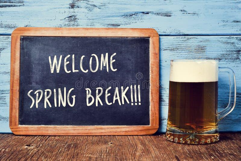 La cerveza y la pizarra con el texto acogen con satisfacción las vacaciones de primavera fotografía de archivo