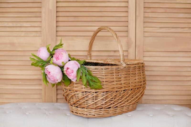 La cesta con la peonía florece en un fondo de madera fotografía de archivo