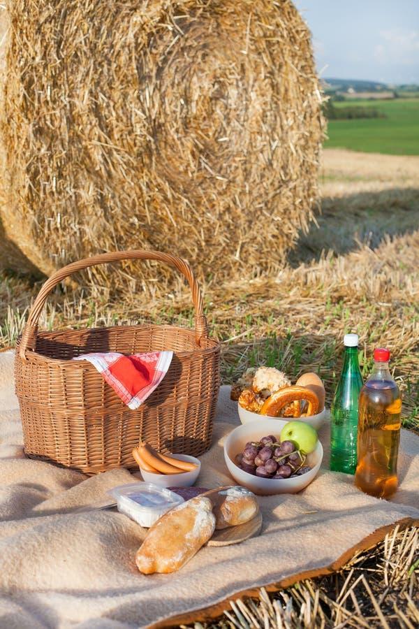 La cesta de la comida campestre y la diversas comida y bebidas en la paja colocan fotos de archivo libres de regalías