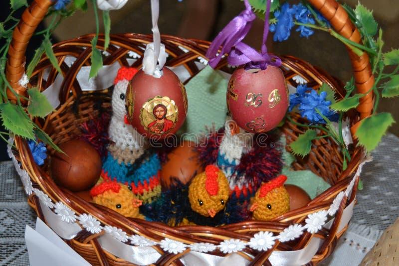La cesta festiva con los huevos de Pascua está en la tabla imagenes de archivo