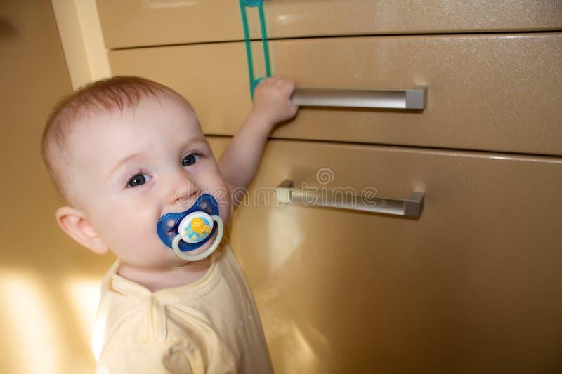 La chéri 8-9 mois essaye d'ouvrir le compartiment de trappe images stock