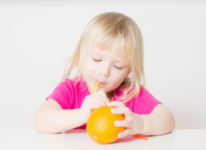 La chéri adorable aspirent le jus de l'orange avec la paille photo libre de droits