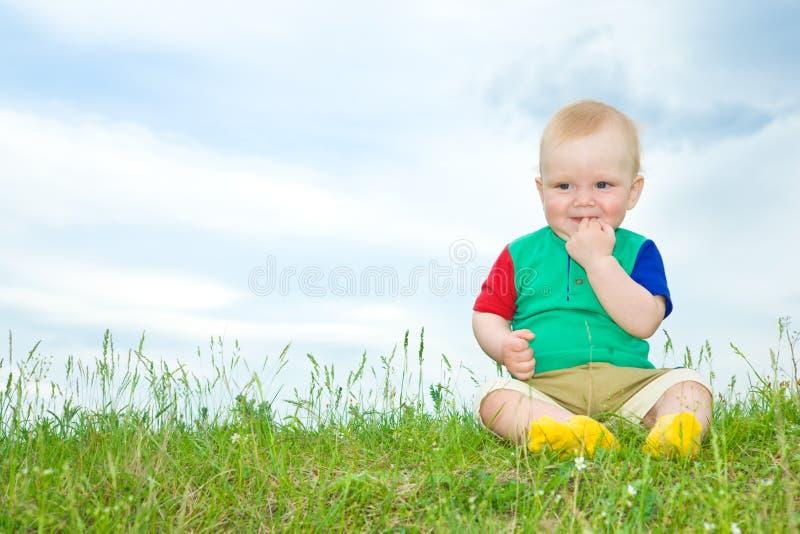 La chéri de Liitle s'asseyent sur l'herbe photos stock