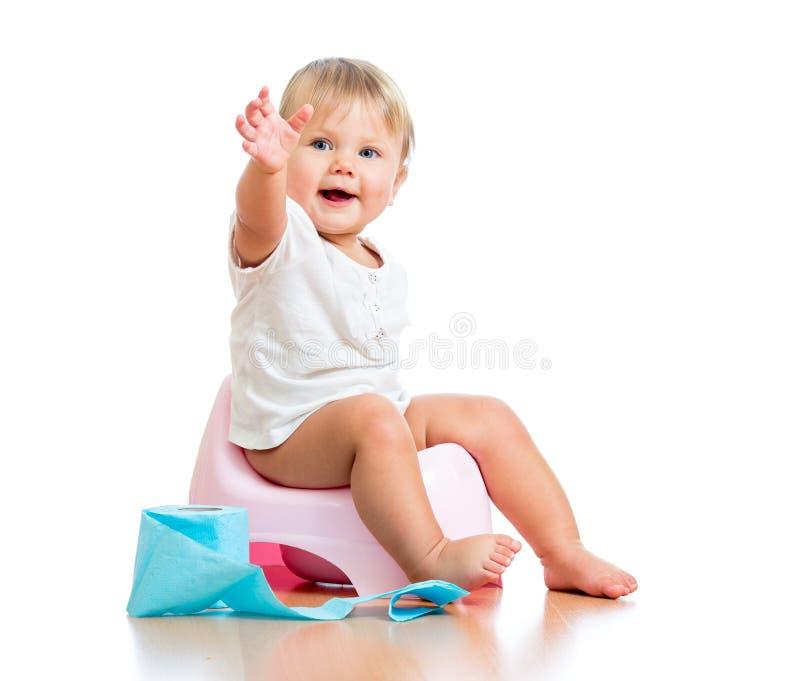 La chéri de sourire sur le bac de chambre avec du papier hygiénique roulent photographie stock libre de droits