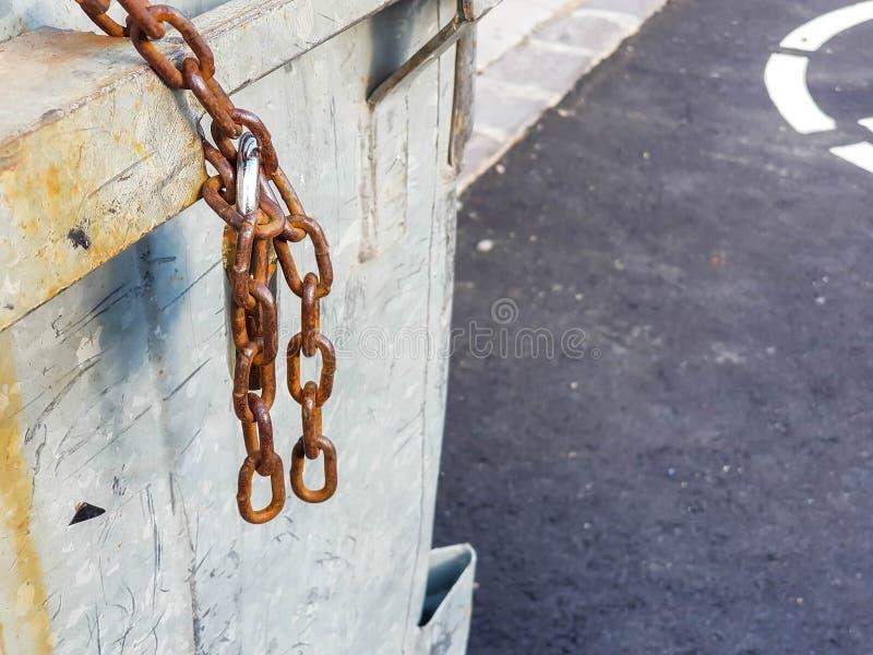 La chaîne rouillée a fermé à clef avec le cadenas sur la poubelle en acier images libres de droits