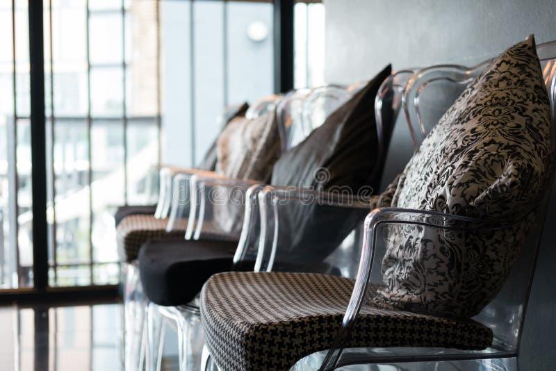 la chaise en plastique transparente avec le coussin et le tissu se reposent photographie stock