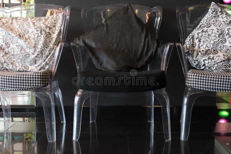 la chaise en plastique transparente avec le coussin et le tissu se reposent images libres de droits