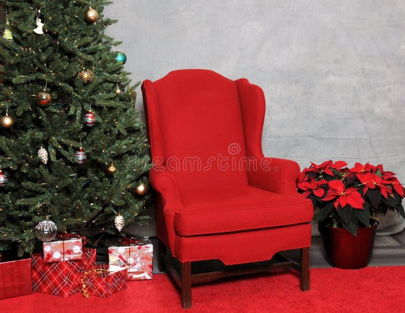 La chaise rouge de Santa avec des cadeaux et un arbre de Noël décoré photos stock