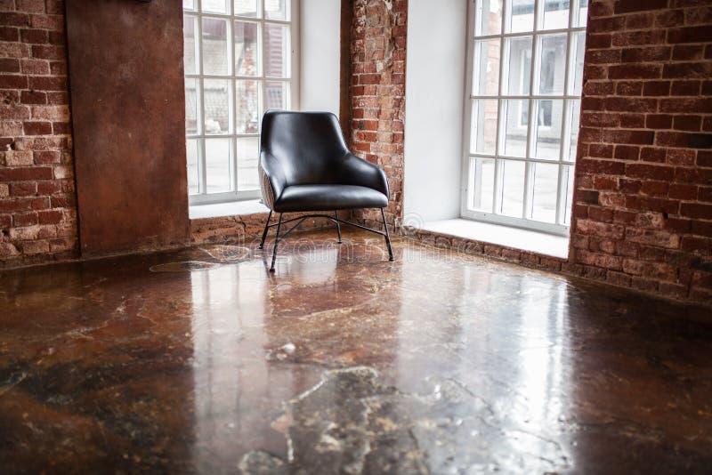 La chaise se tient près d'une fenêtre sur le fond de mur de briques dans W images libres de droits