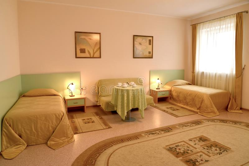La chambre à coucher avec deux lits et un sofa dans le style classique photo stock