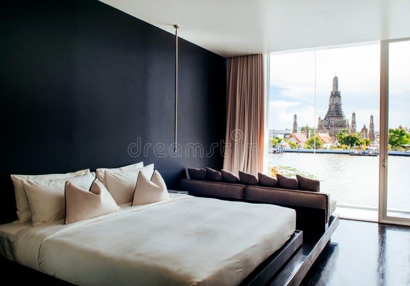 La chambre à coucher avec le lit blanc de mur noir, oreillers couchent, lampe Vent de baie image stock