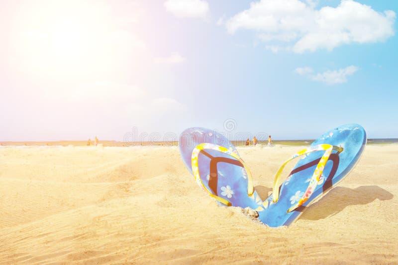 La chancleta azul de la sandalia en la playa blanca de la arena con el fondo azul del mar y del cielo en vacaciones de verano cop imagen de archivo