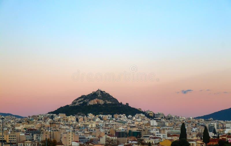 La chapelle de St George a regardé au-dessus des dessus de toit d'Athènes Grèce au coucher du soleil photos stock