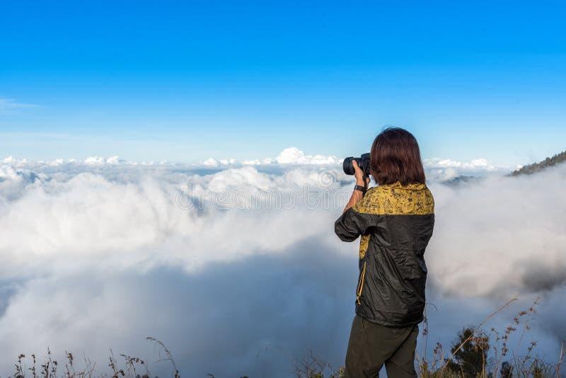 La chaqueta del desgaste del caminante de la mujer, tomando la fotografía, goza y feliz con la opinión superior de la montaña des imágenes de archivo libres de regalías