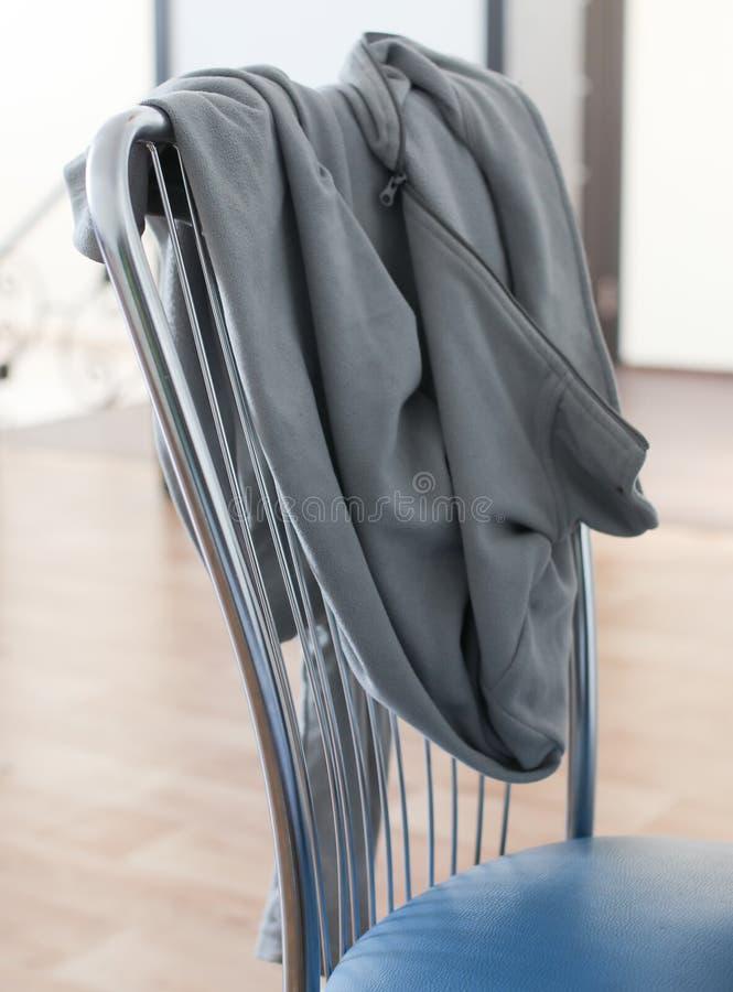La chaqueta está colgando en la parte de atrás de la silla en el cuarto fotografía de archivo