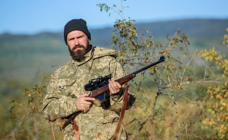 La chasse est passe-temps masculin brutal Homme visant le fond de nature de cible Fusil de prise de chasseur Viser des qualificat photos stock