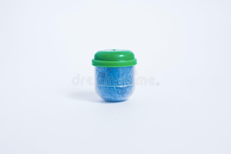 La chaussure bleue couvre les pieds dans une capsule de fond blanc de l'OM de chapeau vert photos stock