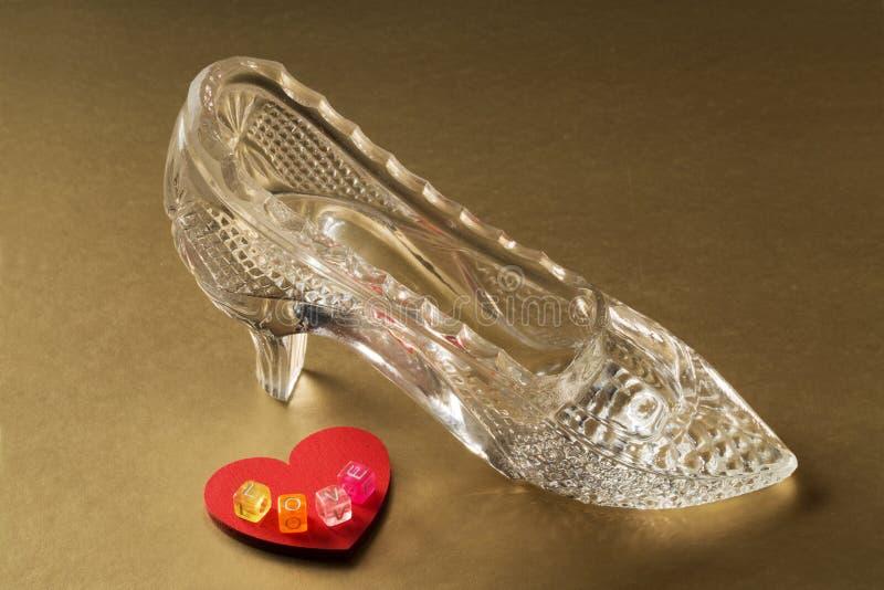 La chaussure en cristal et le coeur rouge avec le mot aiment images stock