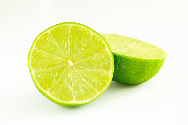 La chaux a coupé dans deux moitiés de couleur verte sur le fond blanc images libres de droits