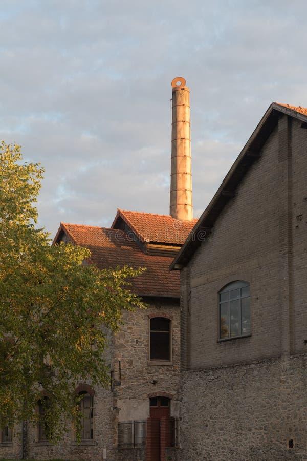 La cheminée ronde s'est allumée par le soleil sur le vieux four de porcelaine de ciel nuageux photo libre de droits