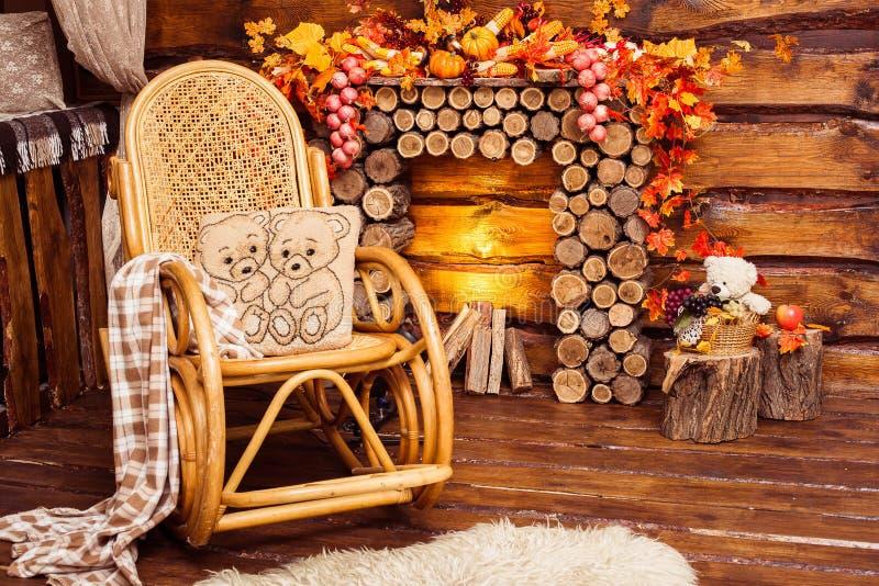 La cheminée s'est rassemblée des rondins, de la basculer-chaise et des fourrures photos libres de droits