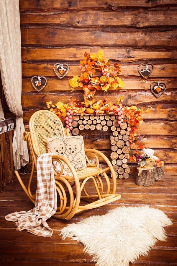 La cheminée s'est rassemblée des rondins, de la basculer-chaise et des fourrures dans le roo photographie stock
