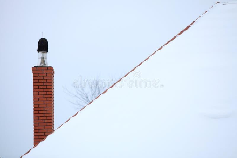 La cheminée sur la neige a couvert le toit photographie stock