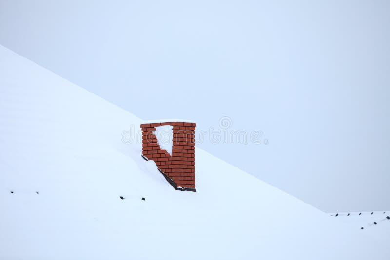 La cheminée sur la neige a couvert le toit image stock