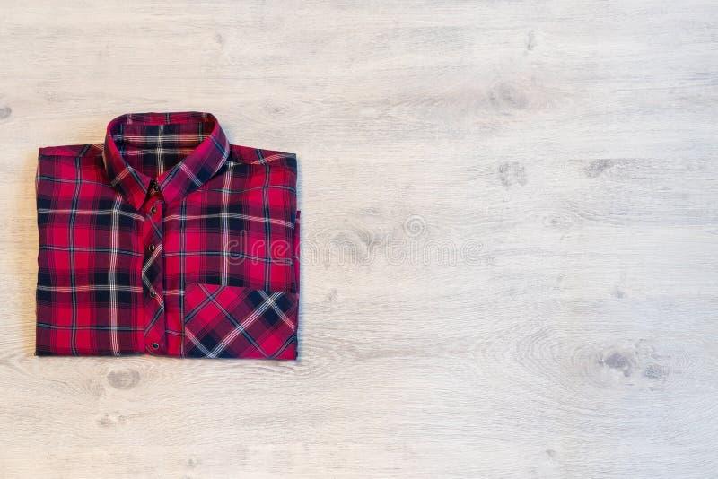 La chemise à carreaux multicolore du ` s de femmes se trouvant d'une manière ordonnée s'est pliée sur un l image libre de droits