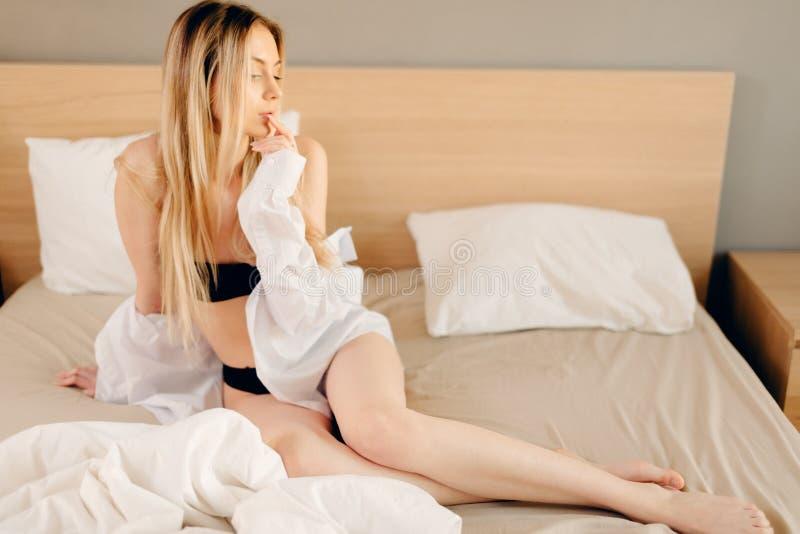 la chemise de l'homme de port de femme blonde d'oung sur le lit Regard vraiment sexy photos libres de droits