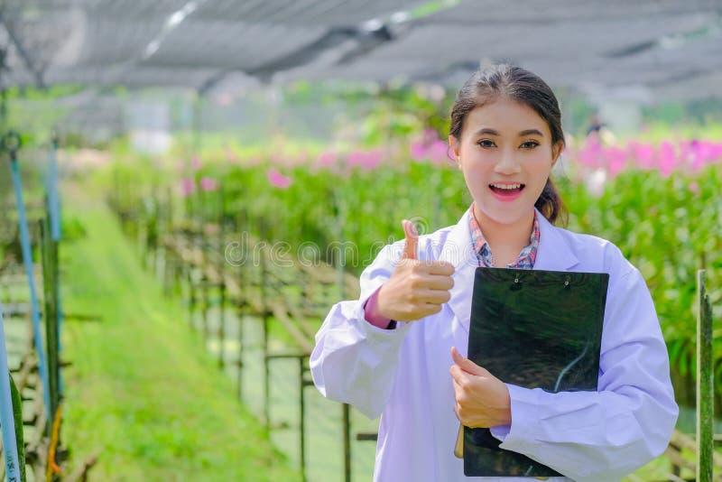La chercheuse de jeune femme dans une robe blanche, manie maladroitement et explore le jardin avant de planter une nouvelle orchi photos stock
