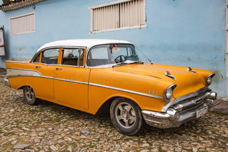 La Chevy classica arancione è parcheggiata di fronte a una casa fotografia stock libera da diritti