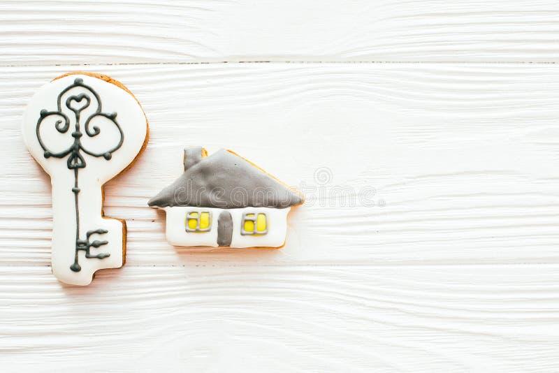 La chiave, casa, biscotti del segno positivo su legno bianco, pone pianamente con spazio per testo Concetto domestico di sogno Ca fotografia stock