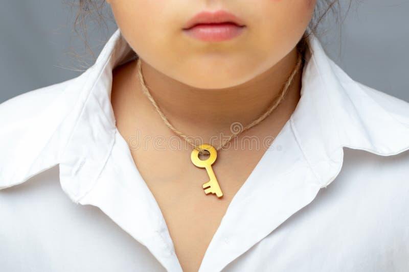 La chiave dorata sul collo del bambino immagine stock libera da diritti