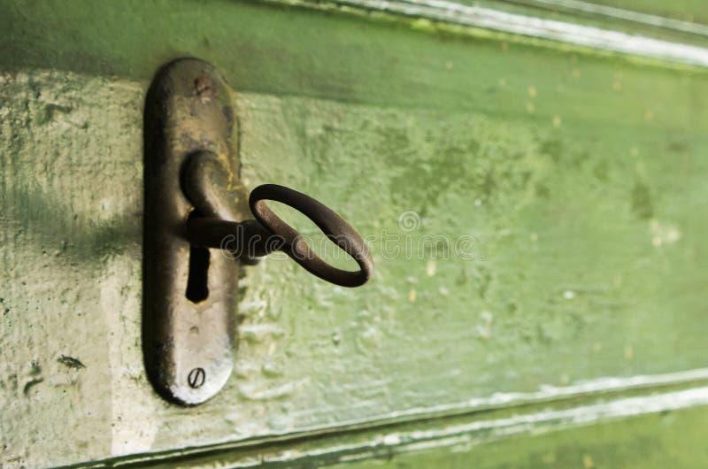 La chiave e fissa la porta di legno verde fotografia stock libera da diritti