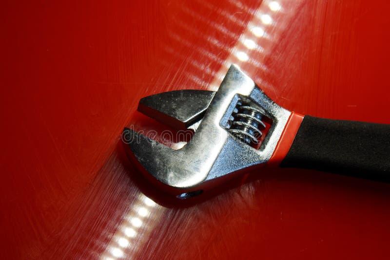 La chiave inglese si trova sulla superficie lucidata rossa nell'officina riparazioni automatica Dispositivi per lavoro del meccan fotografie stock
