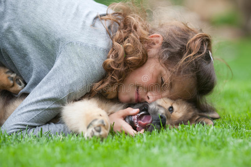La chica joven abraza su perrito fotos de archivo