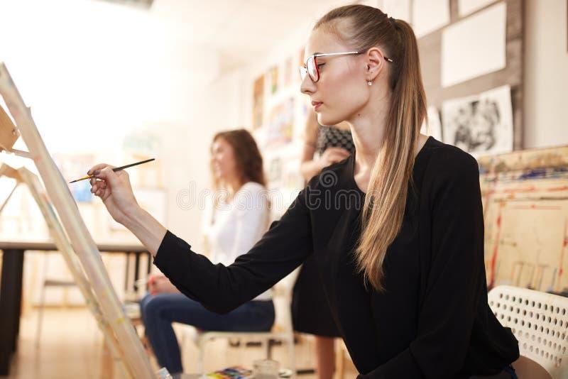 La chica joven agradable en los vidrios vestidos en blusa negra y vaqueros se sienta en el caballete y pinta una imagen en el dib imagen de archivo