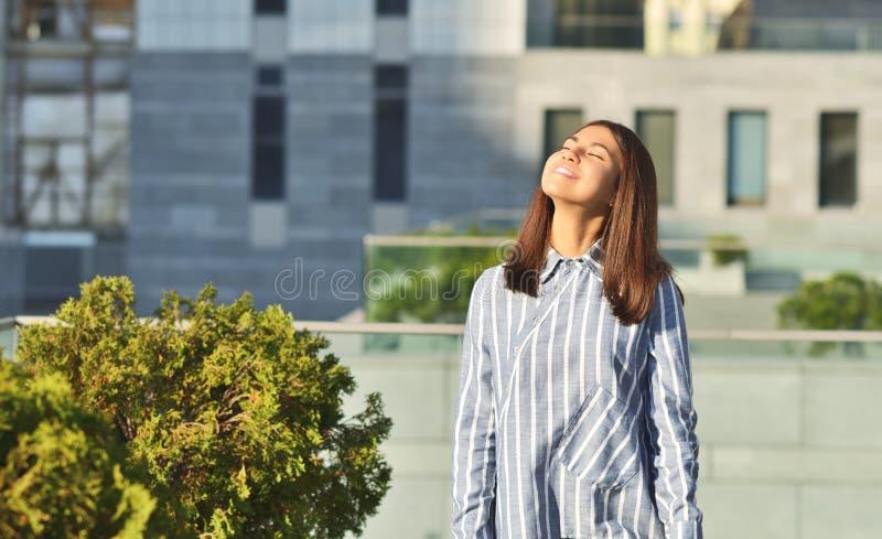 La chica joven asiática está caminando abajo de la calle vistió la camisa rayada azul imagenes de archivo