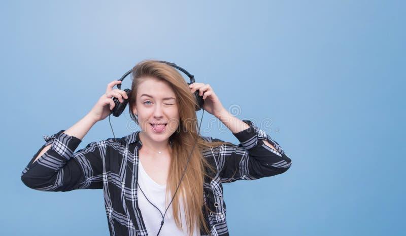La chica joven atractiva con los auriculares está en un fondo azul y miradas en la cámara fotografía de archivo