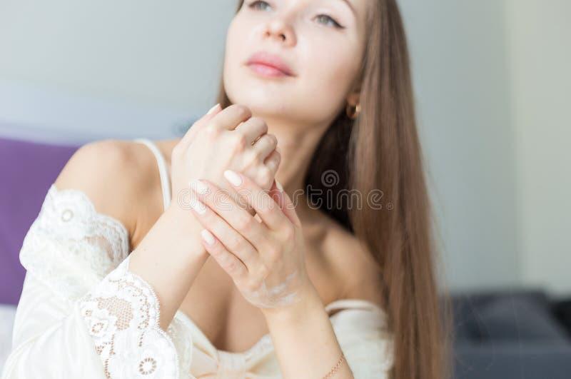La chica joven atractiva en ropa de noche aplica la crema para pelar y la frota mientras que hace procedimientos de la ma?ana moi fotos de archivo