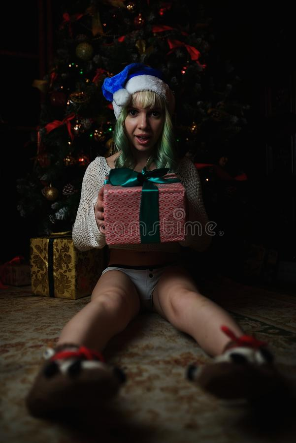 La chica joven atractiva ha recibido el regalo debajo del árbol de navidad fotos de archivo libres de regalías