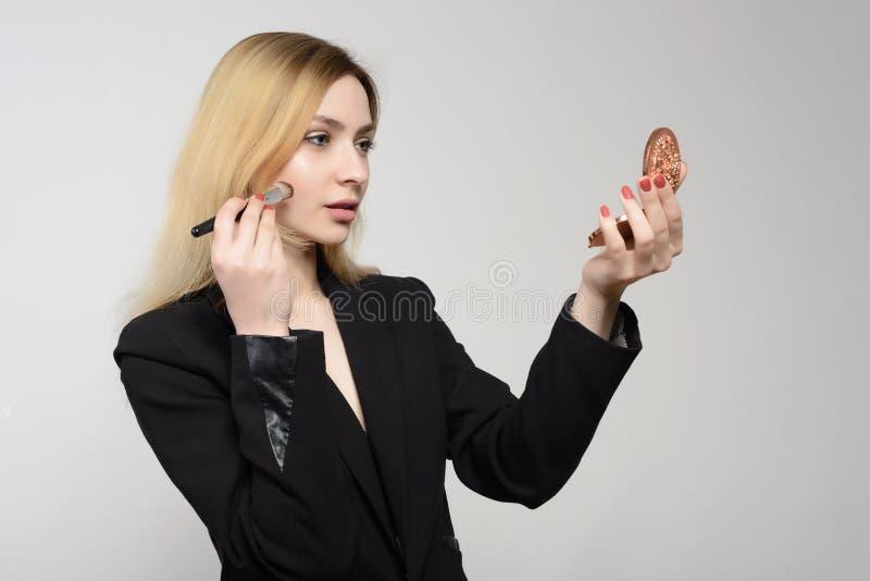 La chica joven atractiva hace el mejk del artista de maquillaje mismo que sostiene un espejo imagen de archivo