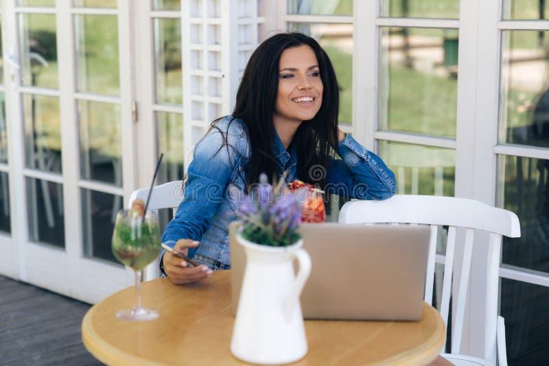 La chica joven atractiva sonriente se sienta en un café, risas, negociaciones alguien El modelo sostiene un smartphone, un ordena foto de archivo libre de regalías