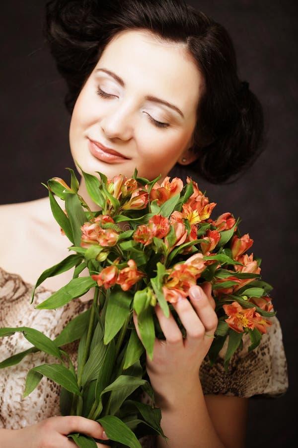 La chica joven atractiva joven sostiene el ramo de flores rojas y amarillas imagenes de archivo