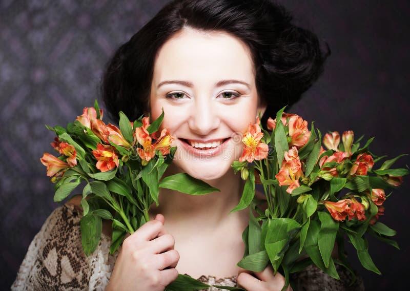 La chica joven atractiva joven sostiene el ramo de rojo y de amarillo imagenes de archivo