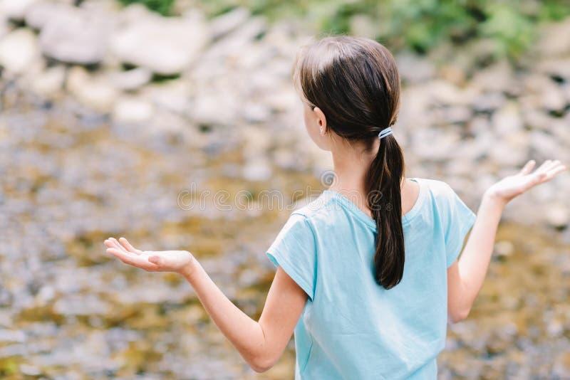 La chica joven aumenta sus brazos que ruega en los bancos de una corriente de la montaña imagenes de archivo