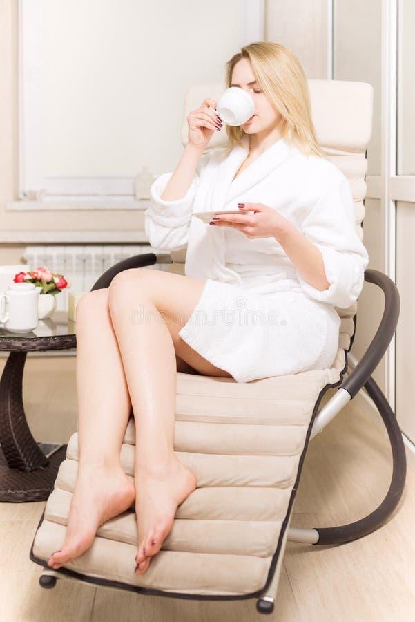 La chica joven bebe té en el salón del balneario mujer rubia en la capa blanca que sostiene una taza en sus manos imagen de archivo